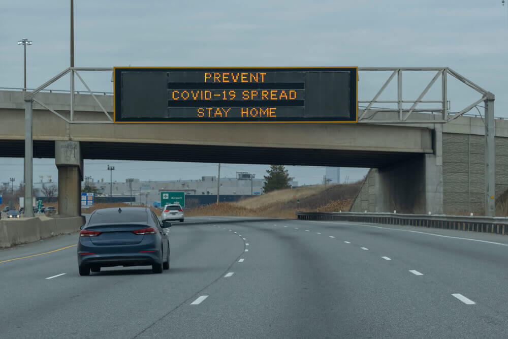 Sign prevent covid-19 spread, stay home on a scoreboard over highway during corona virus pandemic outbreak lockdown